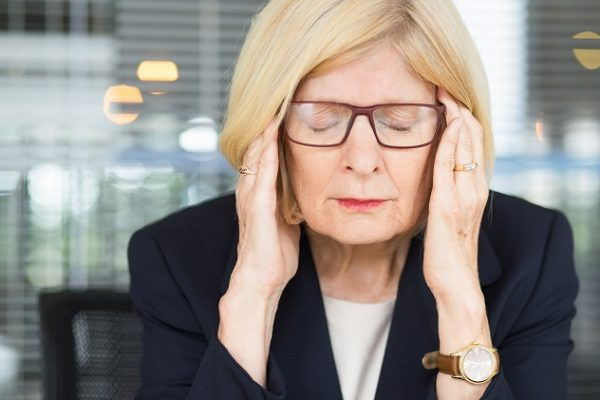 Closeup portrait of stressed attractive senior business woman touching temples, keeping eyes closed and sitting in office
