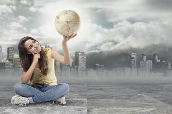 pretty girl sitting on the floor and holding a globe