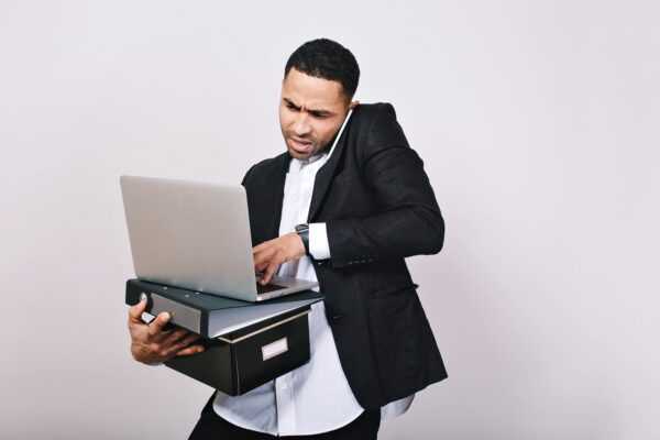 Portrait busy hard-working astonished businessman with office folders, laptop talking on phone on white background. Office worker, career, misunderstanding, smart handsome man